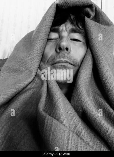 Sick man wrapped in blanket - Stock-Bilder