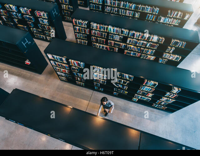 Overhead view of young woman looking for a book in shelf. University student in library selecting a book. - Stock Image