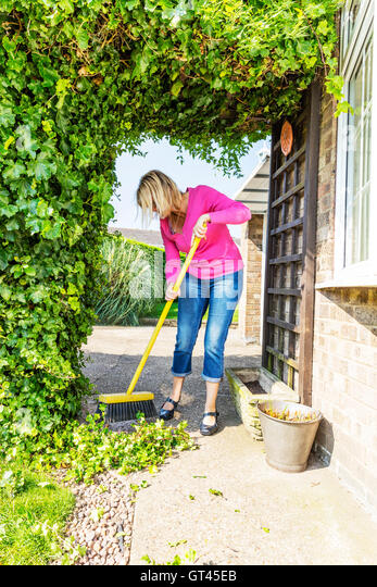 sweeping up mess broom brushing sweep gardening gardener hedge cuttings UK England GB - Stock Image