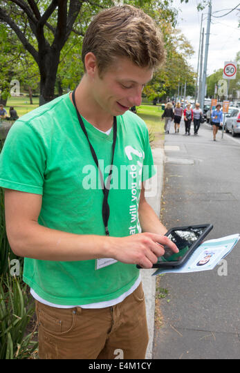Australia Victoria Melbourne William Street Flagstaff Gardens man tablet iPad touch screeen scrolling ChildFund - Stock Image