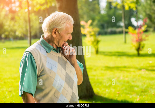 Senior man touching his chin. - Stock Image