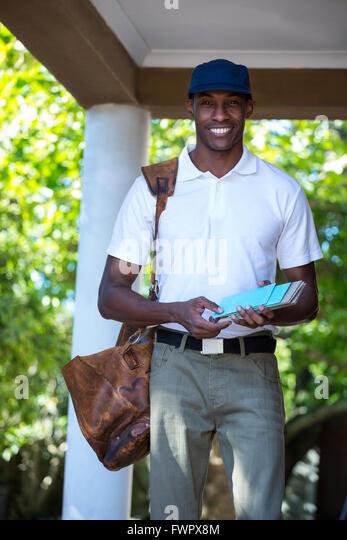 Portrait of postman delivering letter - Stock Image