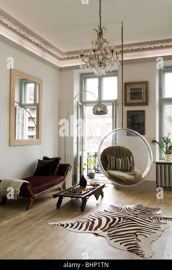 Eero Aarnio bubble chair in living room with zebra skin rug and chandelier - Stock Image