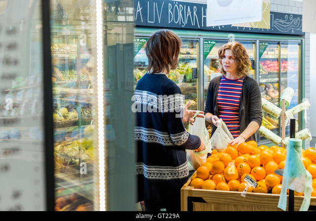 Young woman and man talking while buying oranges in supermarket - Stock-Bilder