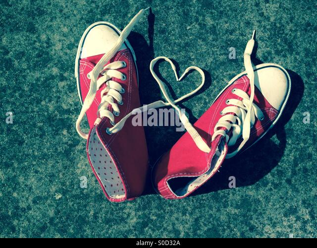 Love heart laces on sports shoes heart shape red baseball boots - Stock Image