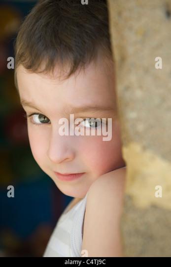 Little boy leaning against tree trunk, portrait - Stock Image
