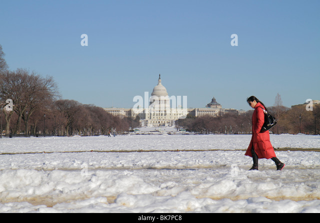 Washington DC The National Mall US Capitol Building woman walking snow winter cold weather coat - Stock Image