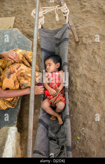 Indian baby girl sleeping in a homemade cradle in a rural indian village. Andhra Pradesh, India - Stock Image