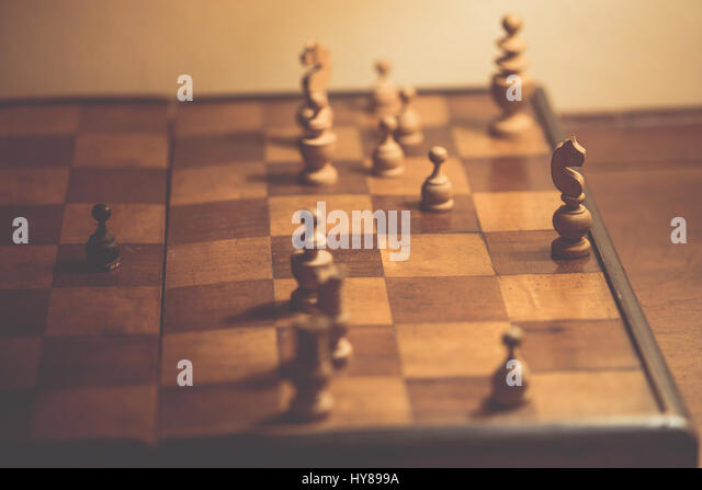 Old chess pieces on a wooden chessboard - Stock Image