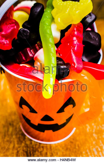 Colourful decorative still life on a kids pumpkin bucket filled with delicious trick or treat lollies. Halloween - Stock Image