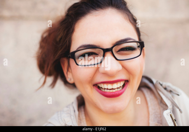 Close up portrait of young woman with toothy smile - Stock Image