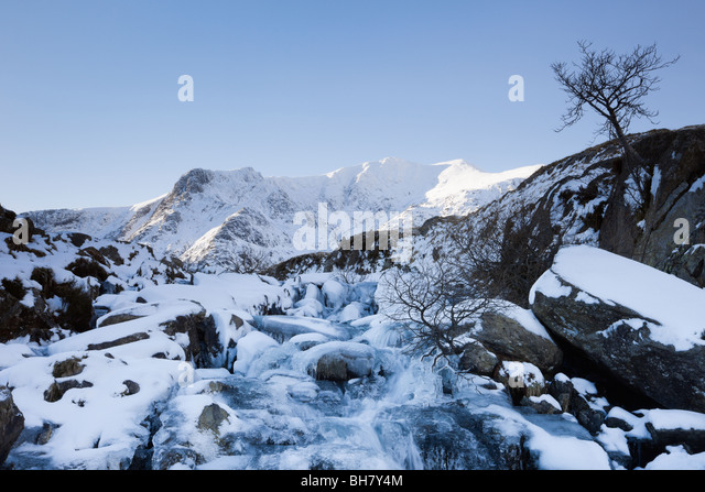 Frozen waterfall with Y Garn mountain beyond in Snowdonia National Park in winter. Ogwen, Gwynedd, North Wales, - Stock-Bilder