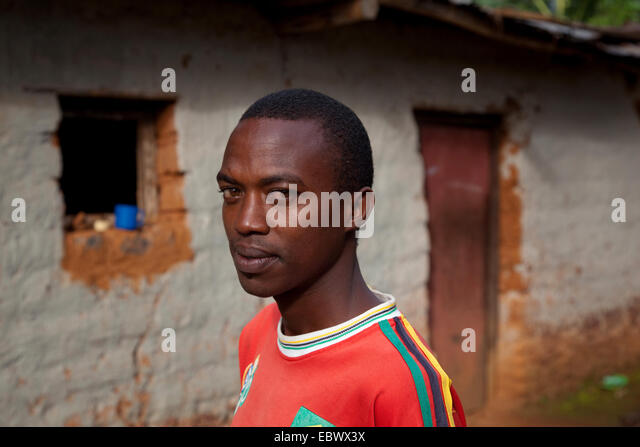 portrait of a young man in front of a humble mud brick house, Burundi, Cankuzo, near National Parc de la Ruvubu, - Stock Image