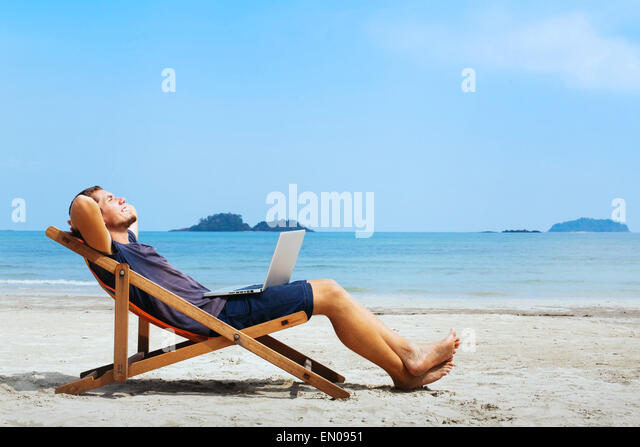 smiling businessman with computer relaxing on the beach - Stock Image