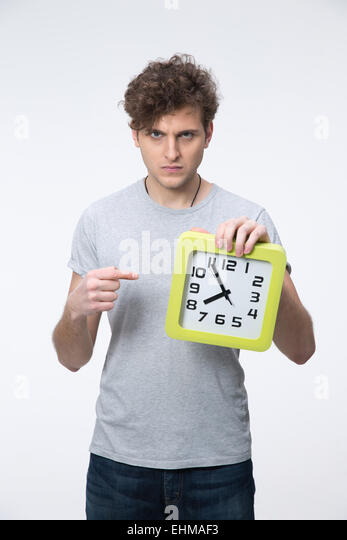 Angry young man with curly hair pointing on the clock - Stock Image