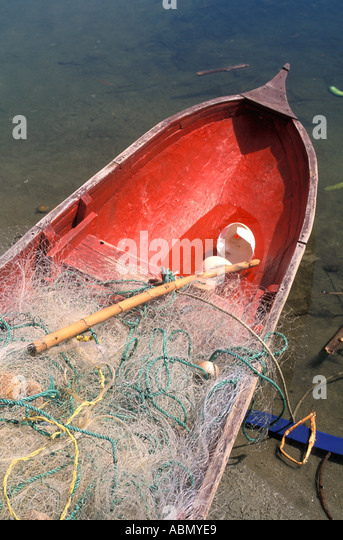 Honduras vertical wooden fishing canoe with fishing nets red bottom plastic water scoop Central America - Stock Image