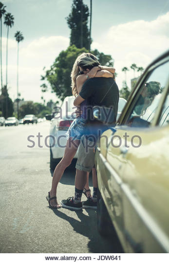 Young couple leaning against car, arms around each other - Stock-Bilder