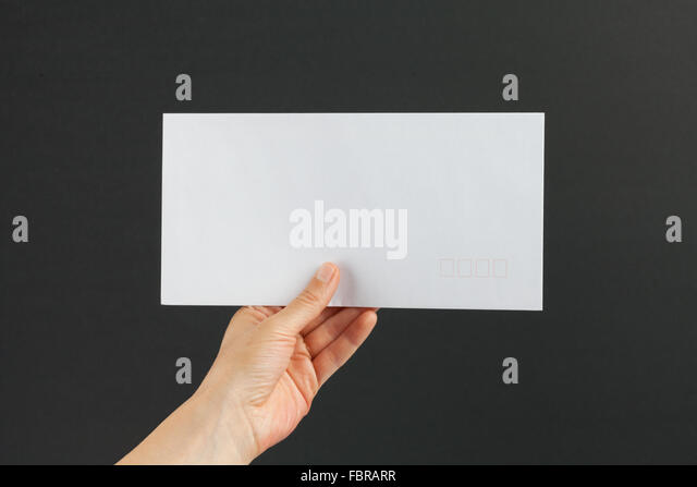 Female hand delivering a white postage envelope on black background - Stock Image