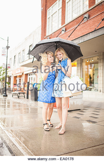 Sisters using smartphone on shopping spree - Stock Image