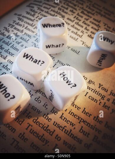 A couple of dice with question words on the page of an open book - Stock-Bilder