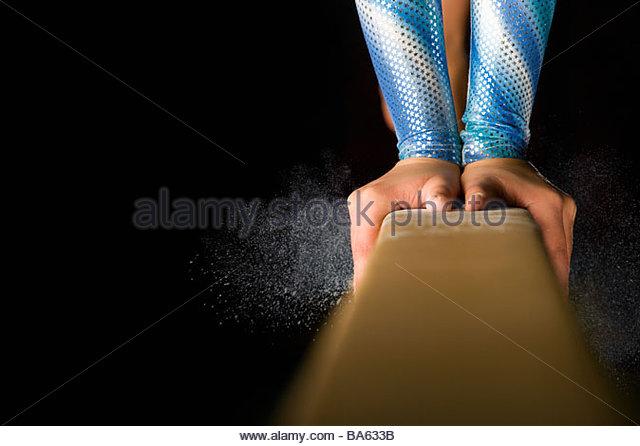 Female gymnast performing on balance beam, close-up of hands - Stock-Bilder