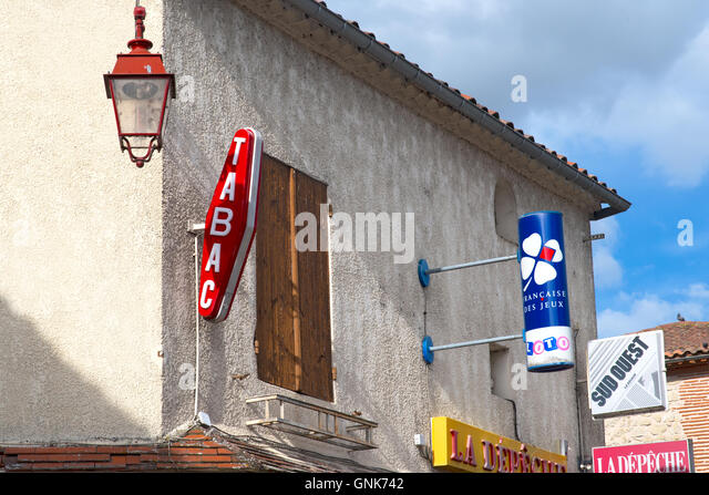 Tabac French advertising hoardings outside of shop with old street light typical - Stock Image