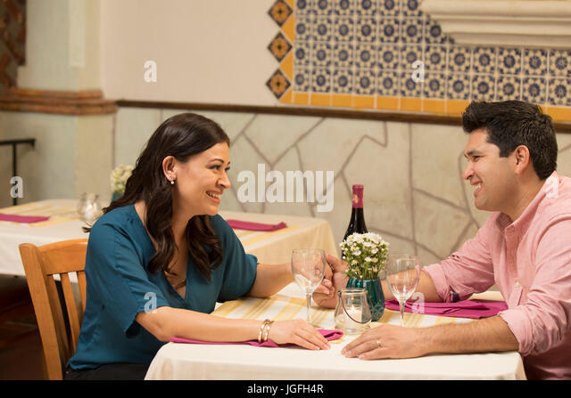 Hispanic couple holding hands at table in restaurant - Stock Image