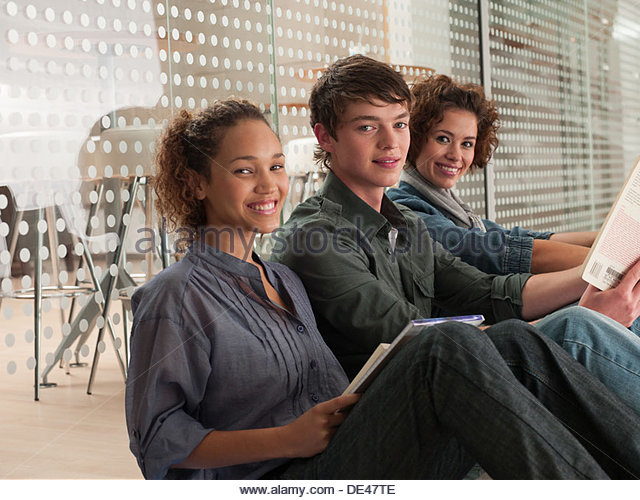 Smiling friends sitting in a row with holding book - Stock Image