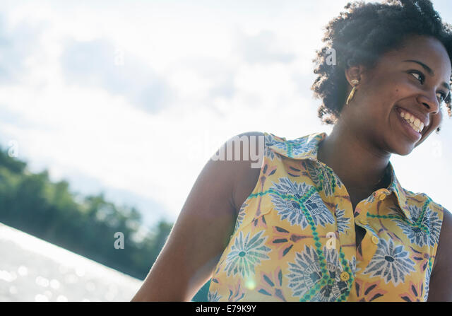 A woman smiling and laughing on a lake shore. - Stock Image