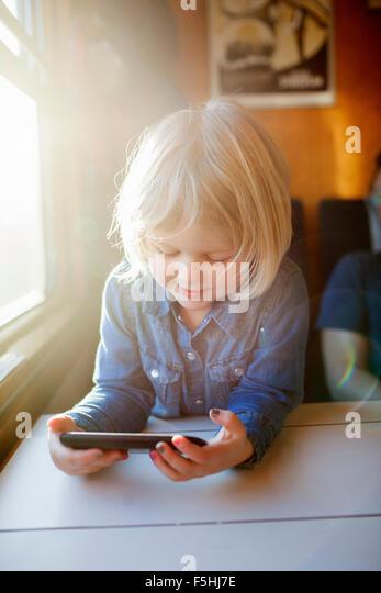 Sweden, Girl (2-3) using smart phone on train - Stock Image