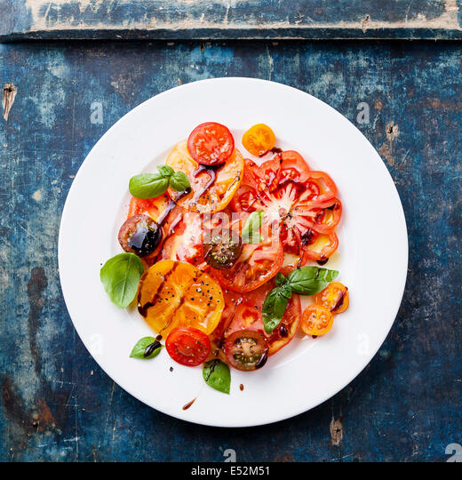 Ripe fresh colorful tomatoes salad with olive oil and balsamic vinegar on blue wooden background - Stock-Bilder