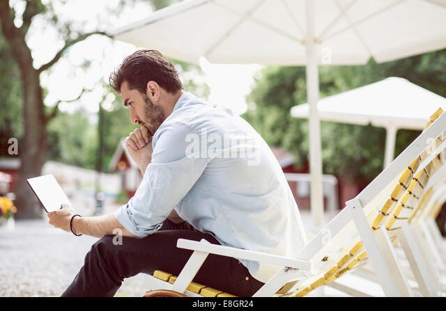Side view of businessman using digital tablet on lounge chair at park - Stock Image
