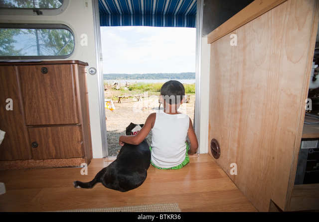 boy and dog sitting in camper doorway - Stock Image