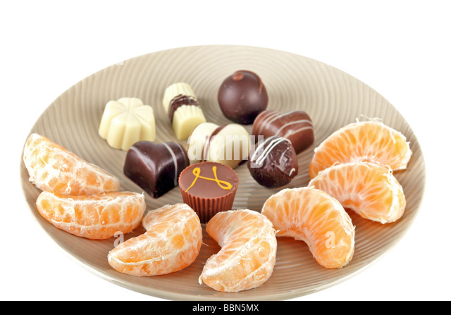 Selection of dark and white specialty chocolates on a plate with mandarin segments - Stock Image