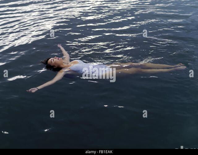 High angle view of woman floating on back in water arms outstretched looking up - Stock Image