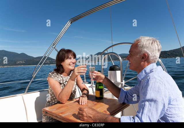 Older couple having champagne on boat - Stock Image
