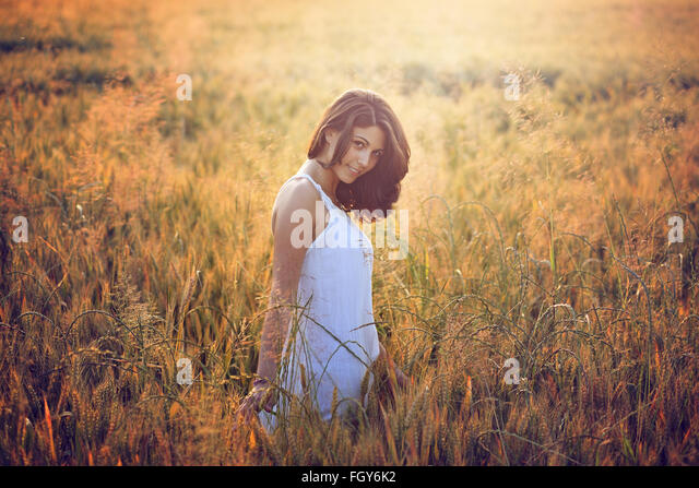 Beautiful young woman in a summer field. Warm sunset light portrait - Stock-Bilder