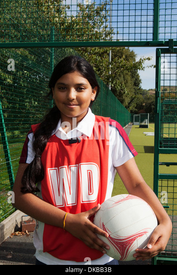 Portrait of schoolgirl netball player with ball - Stock Image