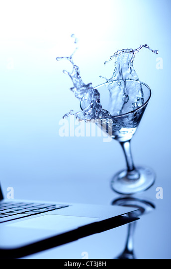 Cocktail spilling on laptop - Stock Image