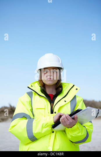 Portrait of female outdoors holding file and digital tablet - Stock Image