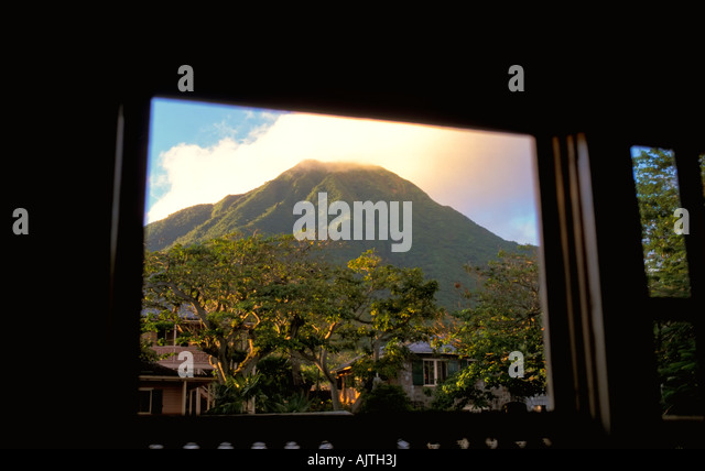 Mount Nevis peak, green volcano crater, Caribbean, seen through window frame, luxury travel, clear blue sky background - Stock Image