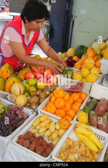 Lima Peru Surquillo Mercado de Surquillo market stall business shopping vendor produce fruits Hispanic woman apron - Stock Image