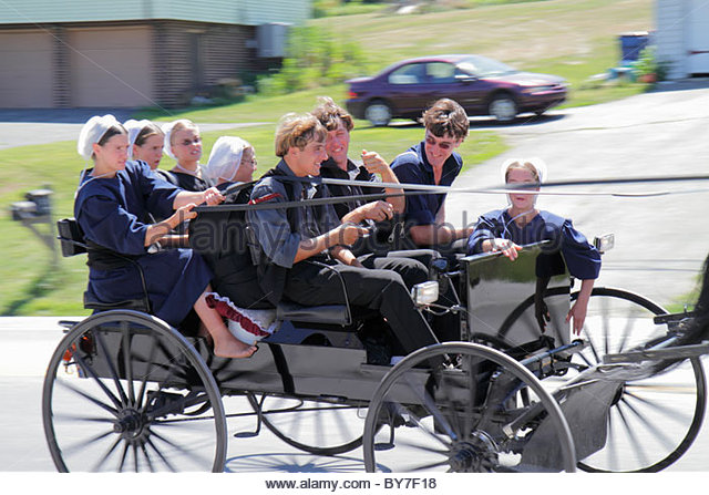 Pennsylvania Strasburg Dutch Country country road Amish community horse-drawn buggy wagon reins girl boy teen adolescence - Stock Image