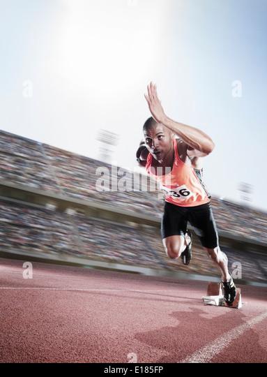 Sprinter taking off from starting block - Stock-Bilder