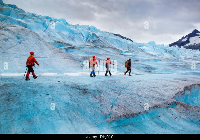 Four people walking on Mendenhall Glacier, Alaska, USA - Stock Image
