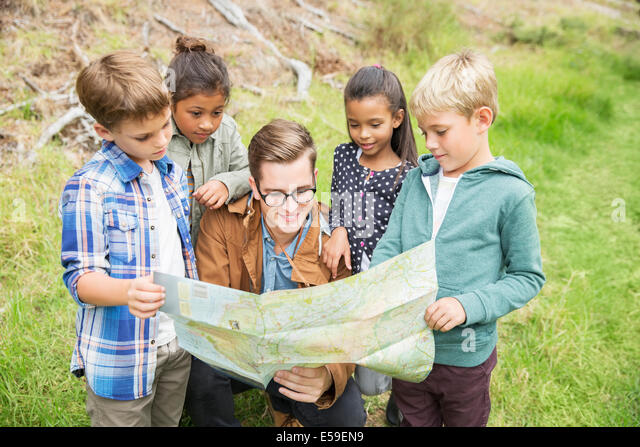 Students and teacher reading map outdoors - Stock Image