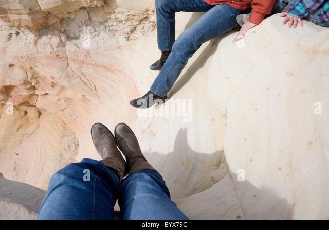 women wearing boots resting on sandstone, high desert of New Mexico, USA - Stock-Bilder