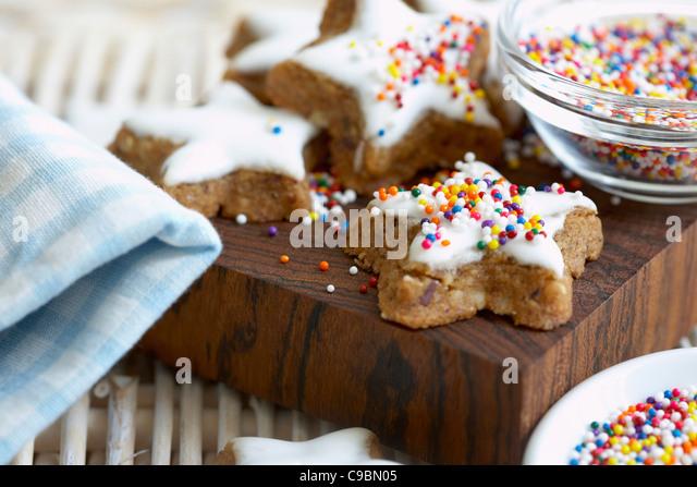 Cinnamon star cookies on chopping board, close up - Stock-Bilder