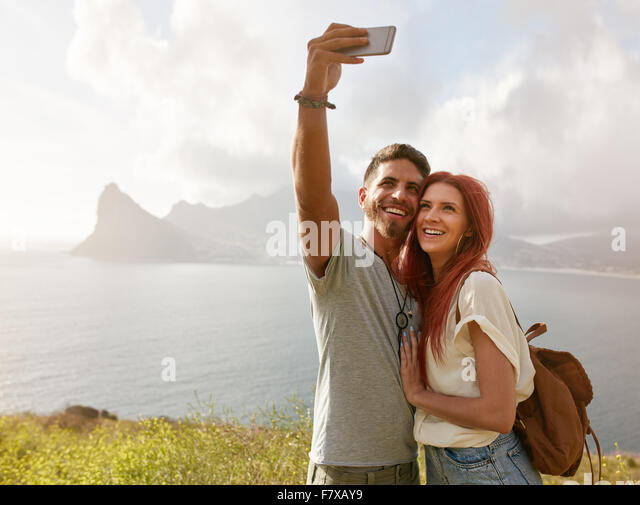 Cheerful young couple on holidays making selfie with smart phone. Young couple by the bay taking a selfie portrait - Stock-Bilder