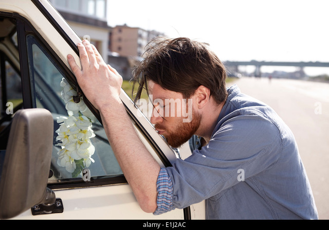 Man kissing front window of a car - Stock Image